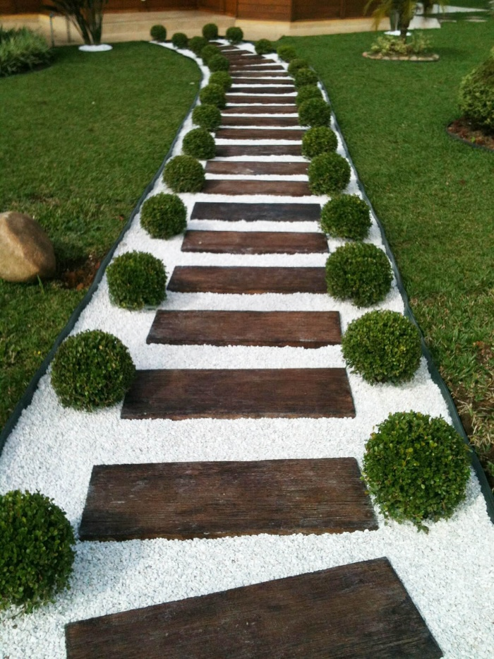beautiful walkway with wooden steps and white stones and green decorative shrubs