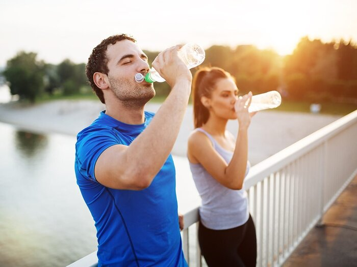 hydration after spot a man and a women drinking water from bottles on a bridge over a river