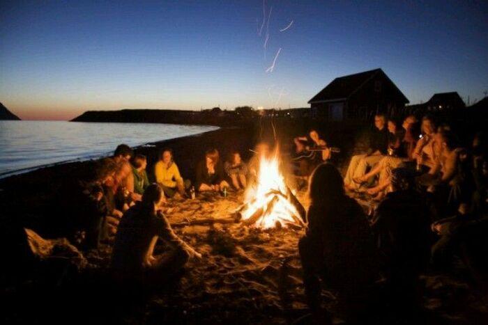 Beach bonfire friends sitting around a fire on the beach talking