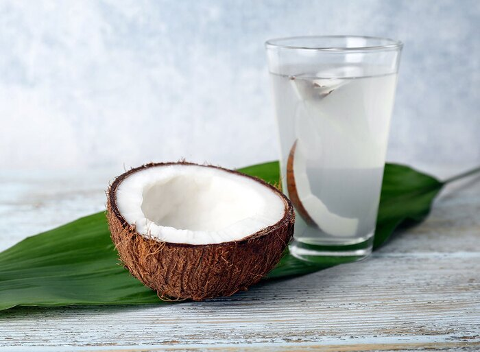 coconut water for optimal hydration half a coconut and a glass of water with a coconut leaf