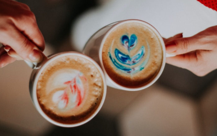two people cheering with two mugs of coffee with cream and colorful applications on it