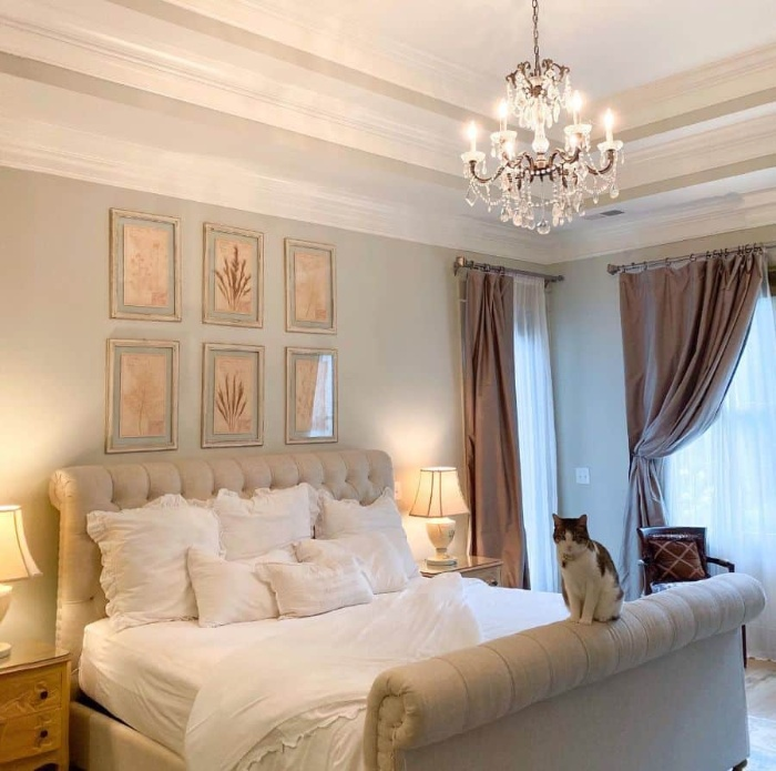 cozy romantic bedroom with a small chandelier and a cat
