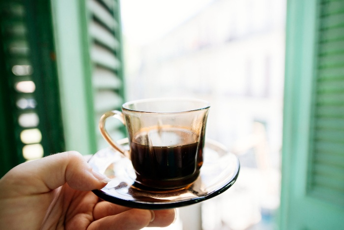 hand holding a glass with cuban coffee in front of a window with green shutters