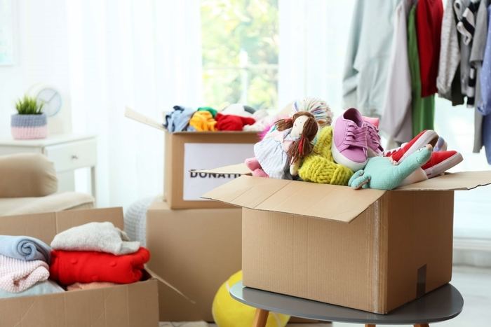 decluttering cardboard boxes full of shoes and other items
