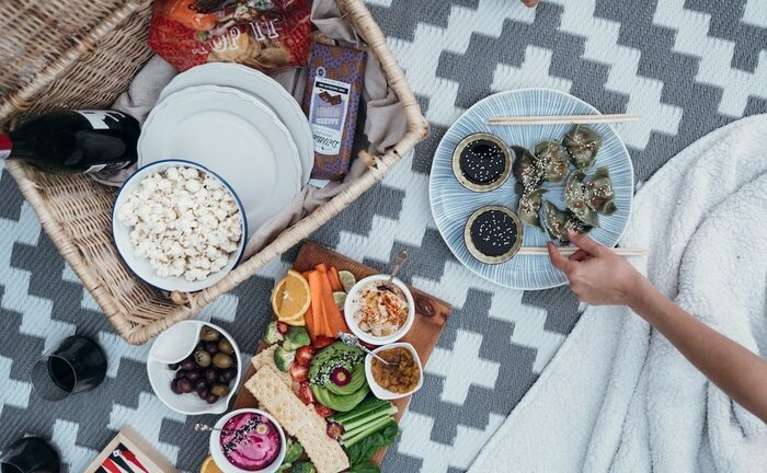 delicious snacks for summer picnic person sitting on a blanket snacking on picnic food