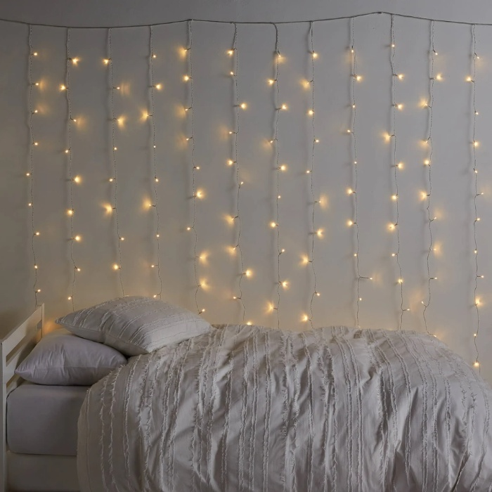 fairy lights on a grey wall over a bed