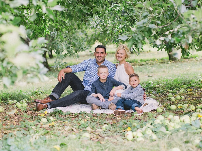 family orchard picnic family of four sitting on the ground under the apple trees