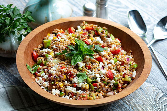 farro salad in a large wooden bowl with two spoons on a grey table