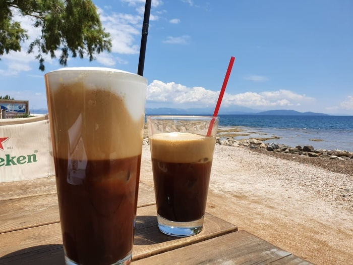 greek frappe on a wooden table on the beach frappe in glasses with straws