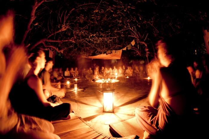 ritual people sitting around lanterns at night celebrating the summer solstice