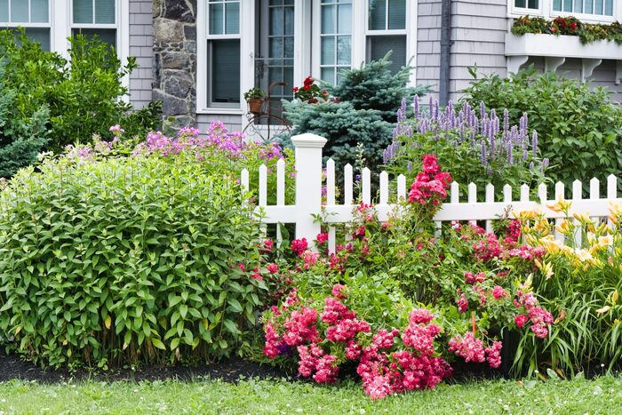 landscape design fence with bushes and flowers