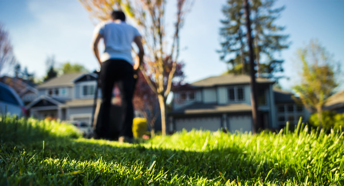 man mowing a lawn with green grass houses in the background