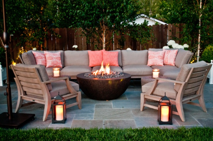 living room outdoors with a fire pit lanterns chairs and a sofa