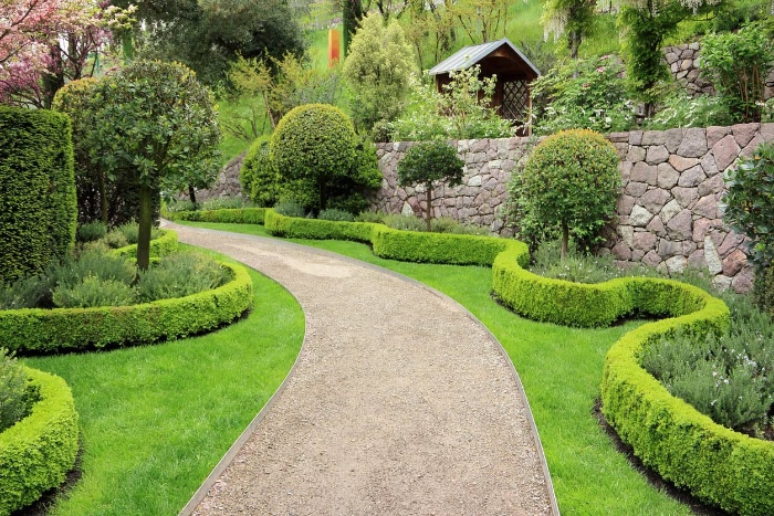 long garden walkway surrounded by green trees and bushes