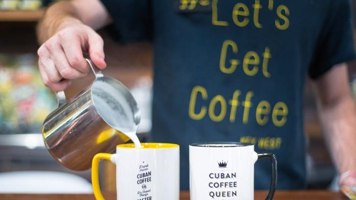 making coffee barista pouring milk into two ceramic mugs making coffee