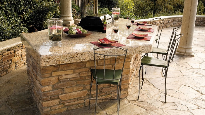 outdoor bar with stone top and iron chairs set for dining