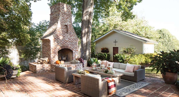 outdoor living room with a huge fireplace and a sitting area with sofa and chairs
