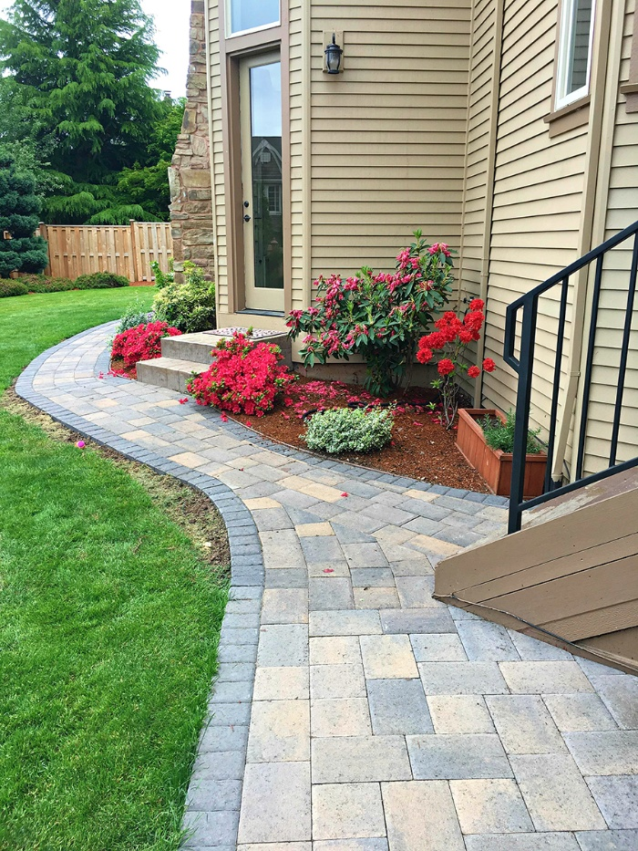 paver pathway in grey and beige around a beige home with flowers in front