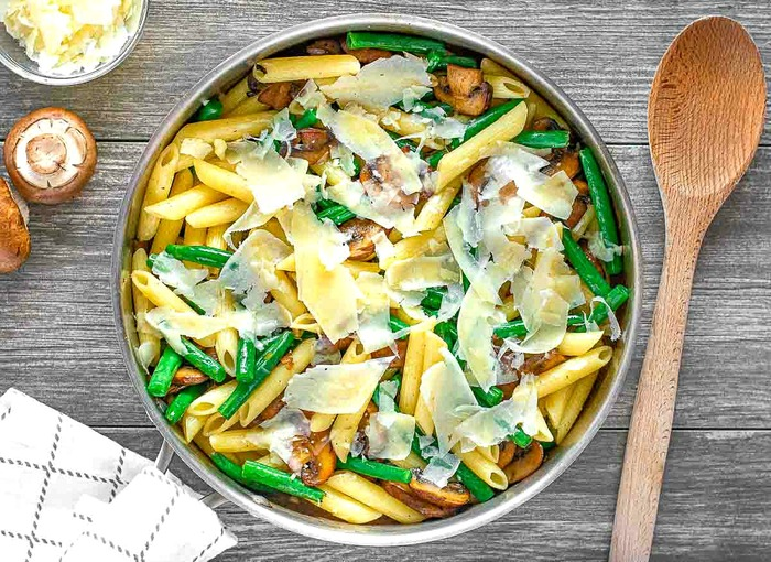 penne green bean meal from above on a table with a wooden spoon