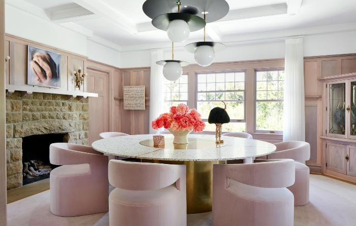 pink interior feminine style with stone table and bright floral centerpiece modern lighting