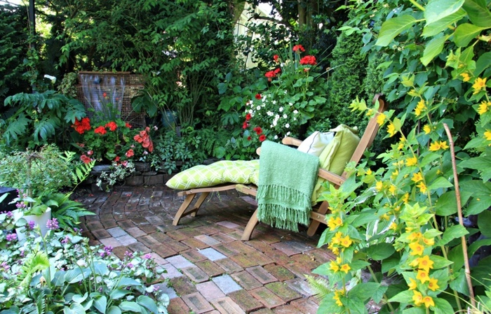 relaxation spot in a garden landscaping with a wooden chair with a blanket and pillow