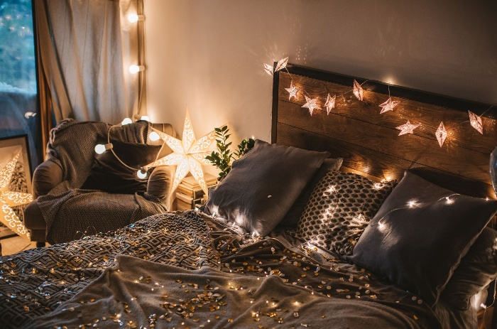 romantic lights in a dark bedroom on a bed and sofa