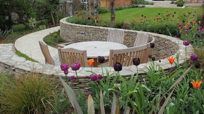 sloped backyard with a wooden table and chairs surrounded by tulips