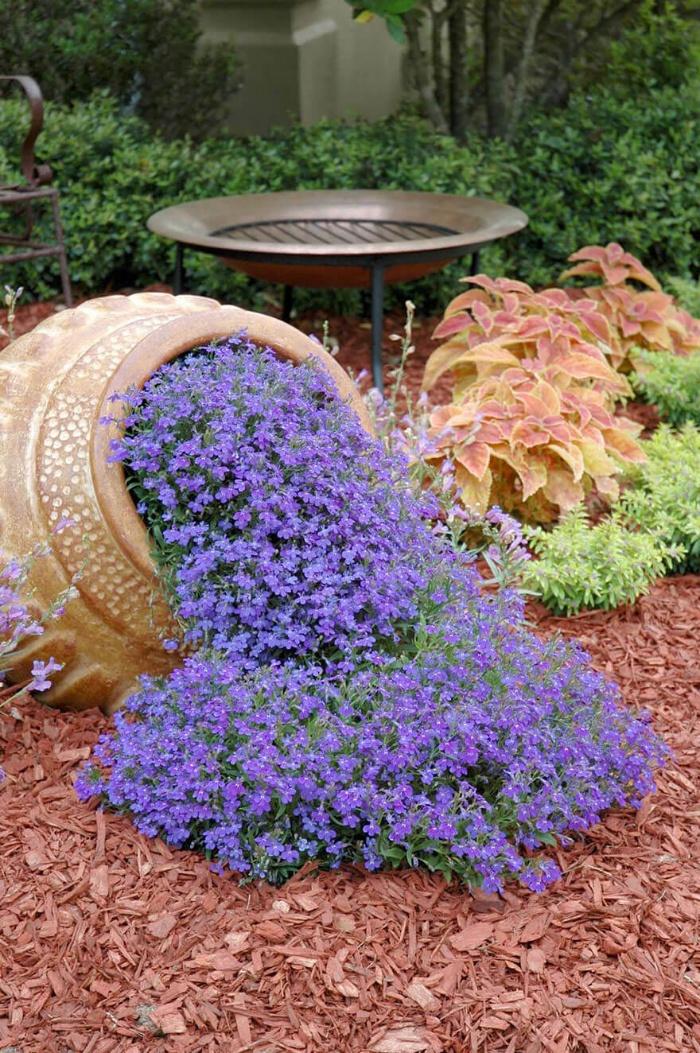 spilling flowers from a huge ceramic jug purple flowers in a garden
