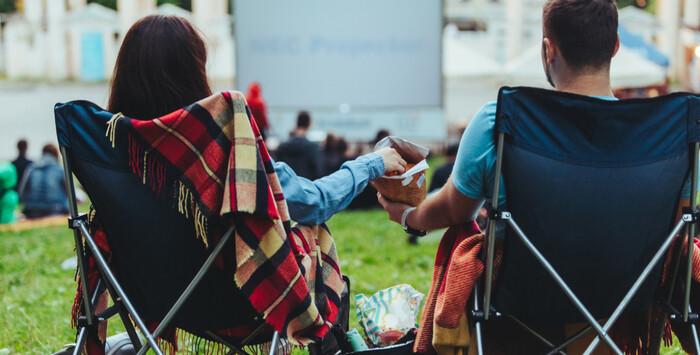 summer movies otudoor cinema couple sitting eating popcorn and watching