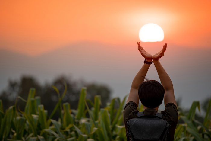 summer solstice day man holding the sun with two hands out in a field