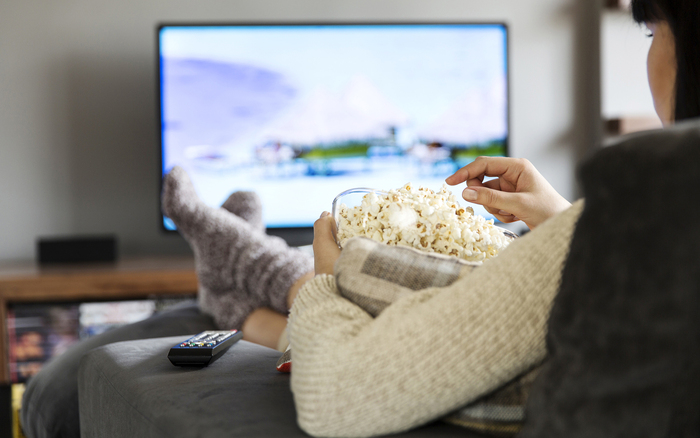 woman in sweater and socks sitting in front of the tv with a bowl of popcorn
