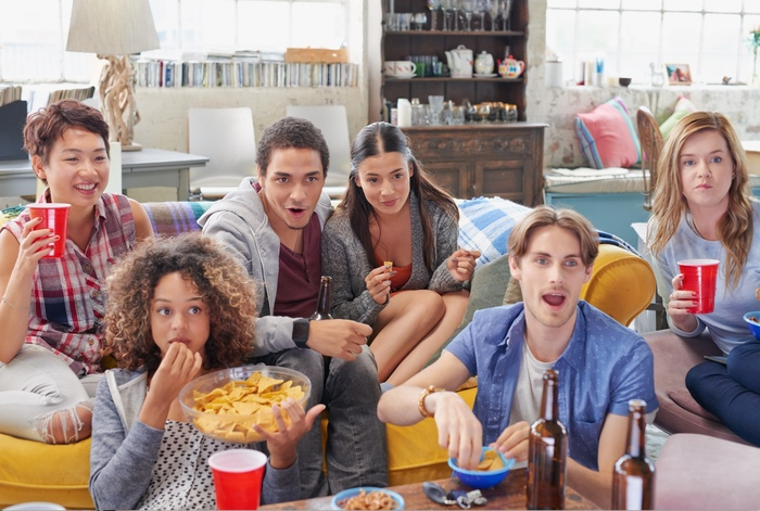 friends watching a movie in a living room with snacks