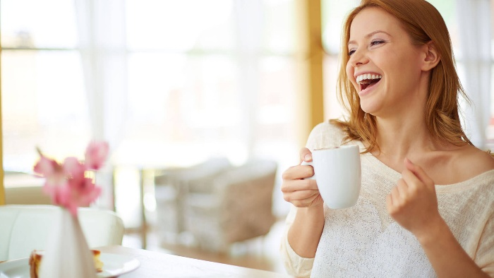 woman drinking coffee in a white mug and laughing