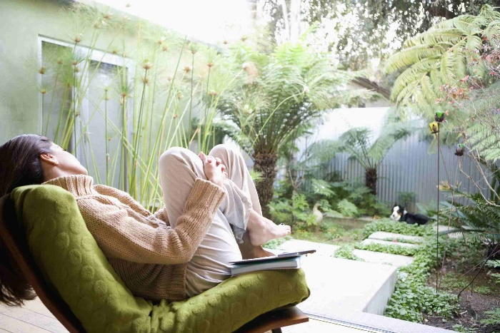 woman patio sitting in a green chair looking at the garden