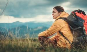 Pleasant nice woman sitting on the grass while enjoying mountain view