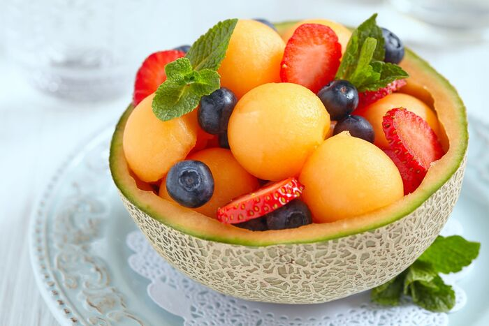 cooling summer dessert fruits in half a melon on a white plate
