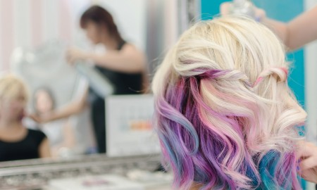 Hairdresser spraying hair spray on the female finished haircut. She love her new look and watching herself in the mirror. Love unicorn and rainbow hair.