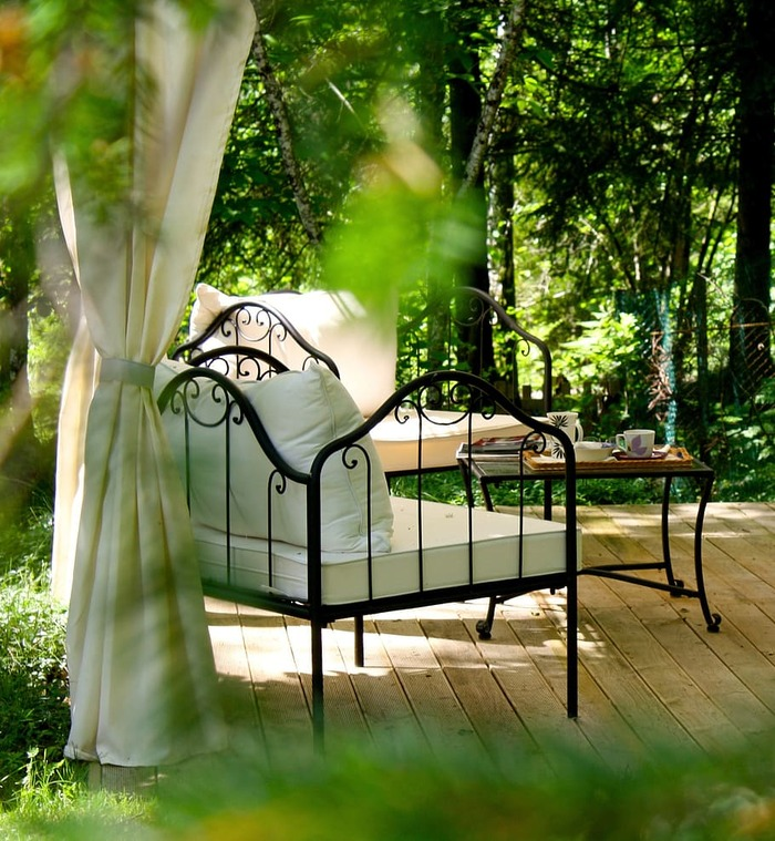 afternoon tea garden relaxation spot with benches and a coffee table surrounded by trees