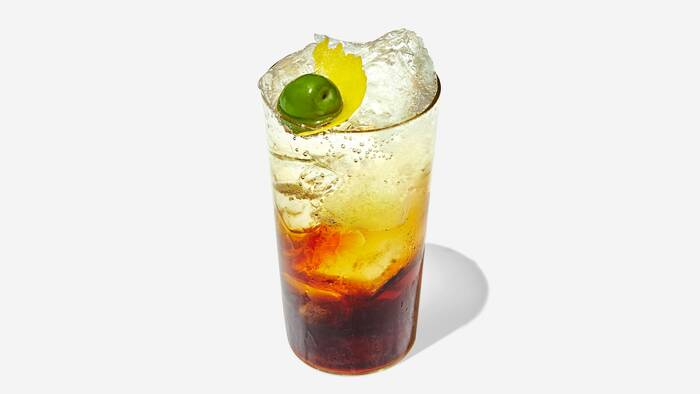 amaro and soda cocktail in a glass filled with ice and decorated with fruits