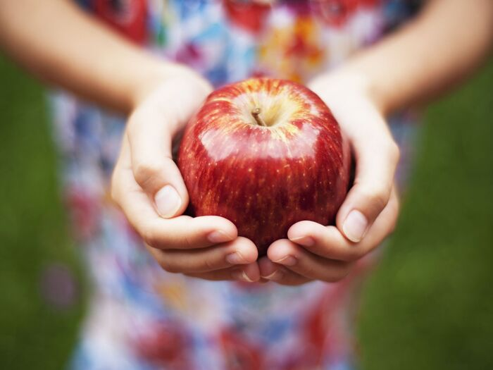 child with a colorful dress holding a red apple in their hands