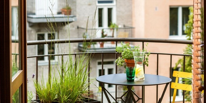 balcony garden small urban balcony with a view small table with a yellow chair and grass plants
