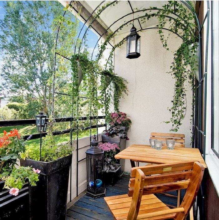 balcony privacy small balcony with a wooden table and chairs living plants a lantern and an arch