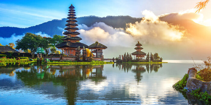 Bali landscape water with temples in the background with mountains and clouds