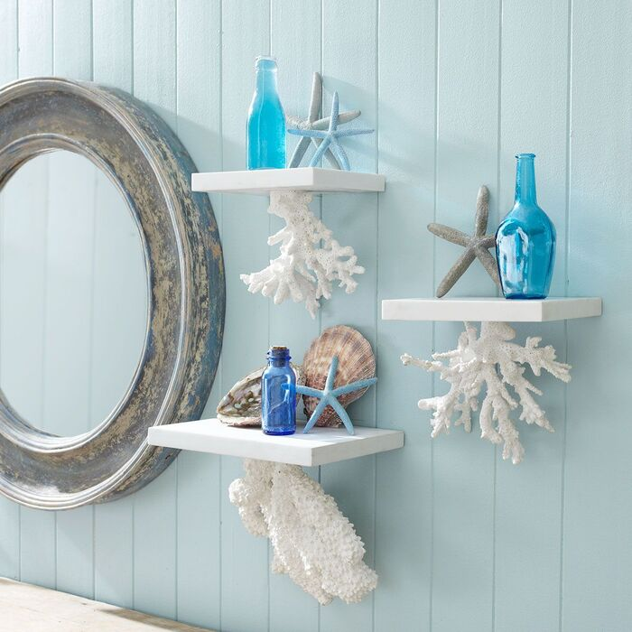 sea themed bathroom decor with a grey mirror and little white shelves with blue bottles and shells