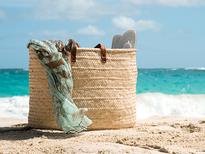 beach bag with a blue scarf coming out of it on the sand with the sea in the background