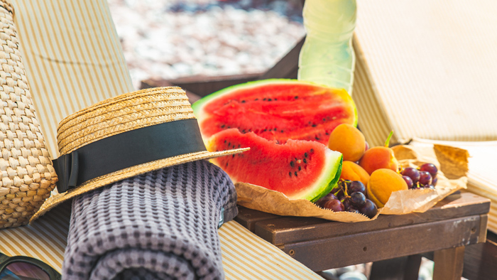 beach accessories sun hat towel summer bag and fruits