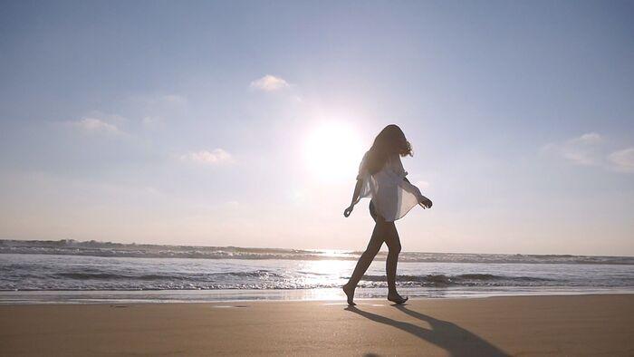 beach walk woman walking on a beach at sunrise