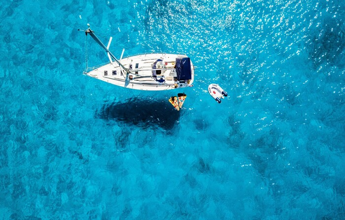 a white boat in the middle on a light blue sea with people lounging in the water