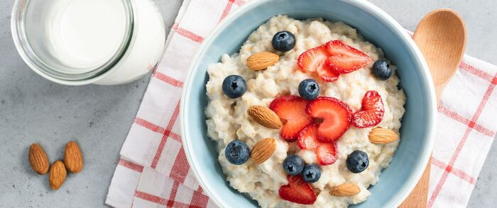 cereal and oatmeal breakfast with fruits and nuts on a white and red towel with a wooden spoon
