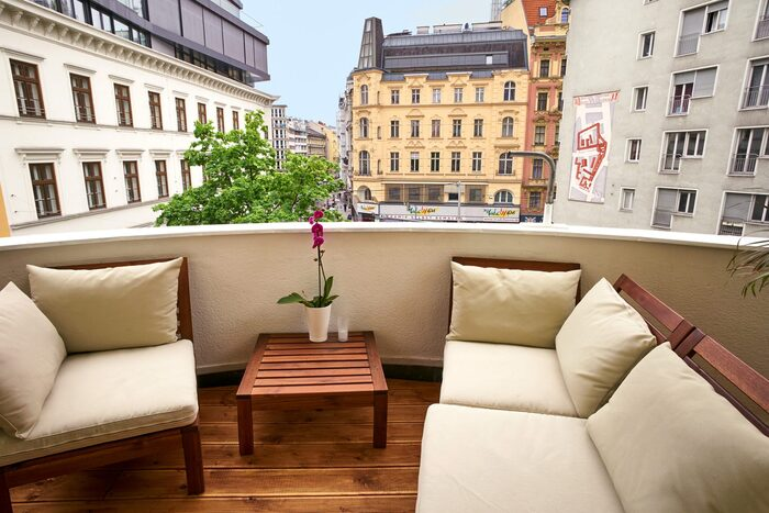 city balcony minimal design with wooden floor beige sofas small wooden table and a nice view